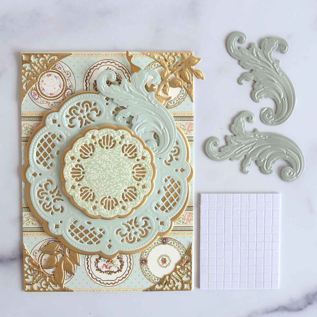 We added the cut flourishes to the card with foam adhesive.