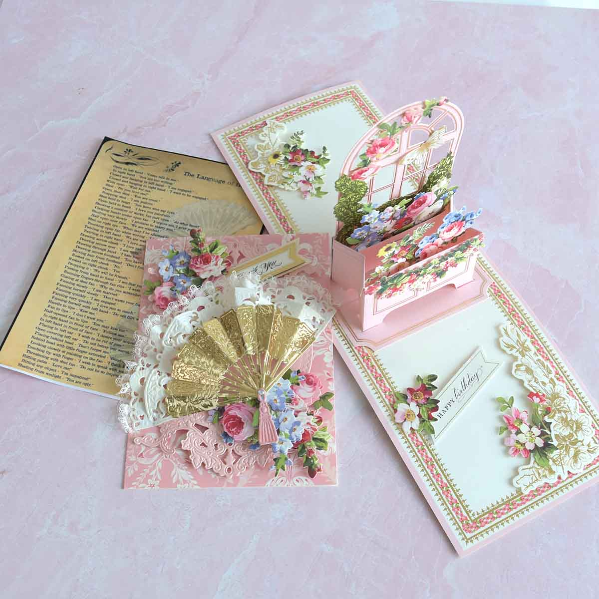 Pink Window Box Card and Pink card with gold and white fan surrounded by pink and blue flowers.