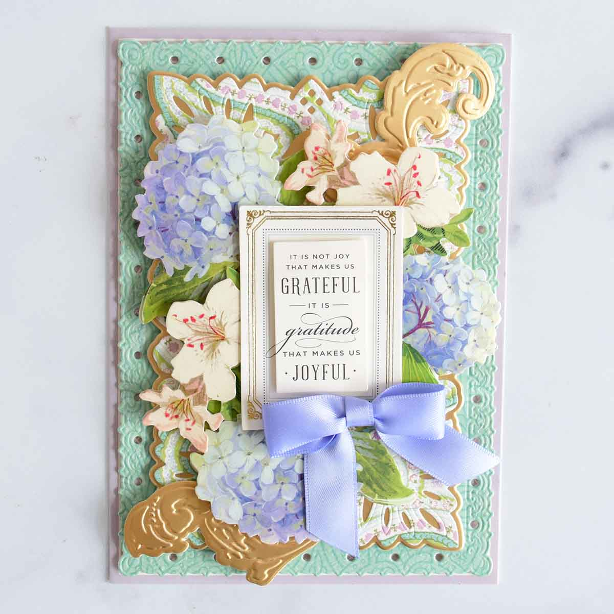 Purple and turquoise card with patterned layers, hydrangeas and azalea stickers, a sentiments and periwinkle bow.