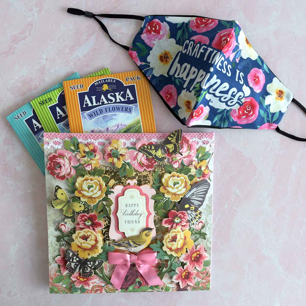 floral card with yellow and pink flowers, butterflies, birds, a pink bow and sentiment that reads Happy Birthday Friend.There are also packets of Alaska wildflowers and a mask that reads Craftiness is Happiness.