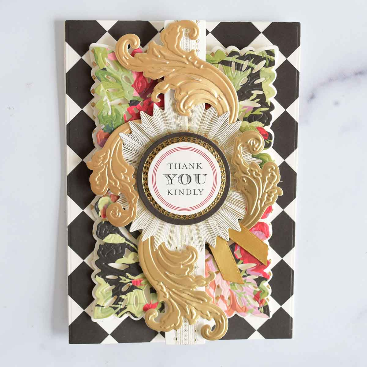 A black and white checkered card base has a patterned layer, a collage card topper and 4 gold flourishes added.
