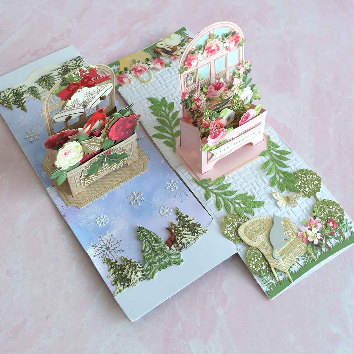 Two window box cards one is blue and Christmas themed and the other is a pink floral garden with foliage.