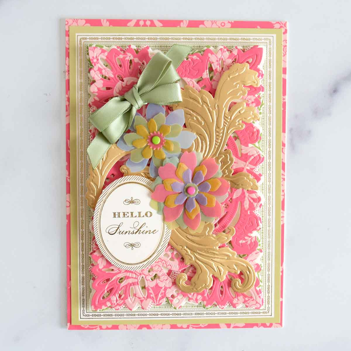 A pink damask card with green bordered layer and pink damask layer. There are two 3D flowers and 3 gold flourishes, a Hello Sunshine sentiment and sage double bow.