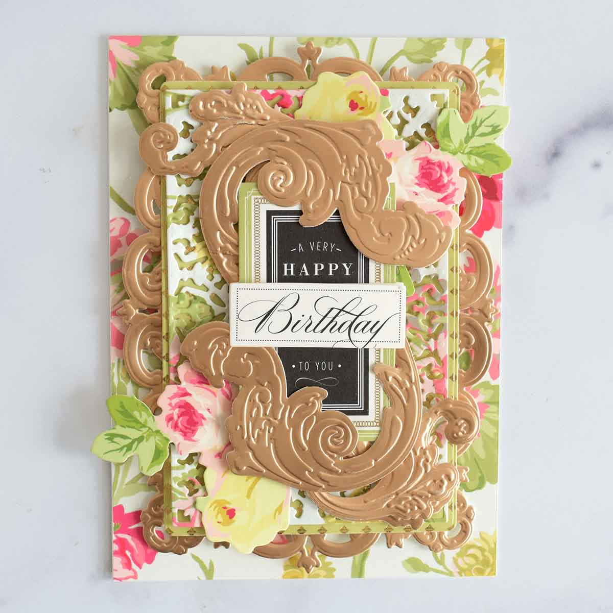 A floral card with rose gold layer, green layer and floral layer with 4 layered rose gold flourishes and A Very Happy Birthday To You sentiment.