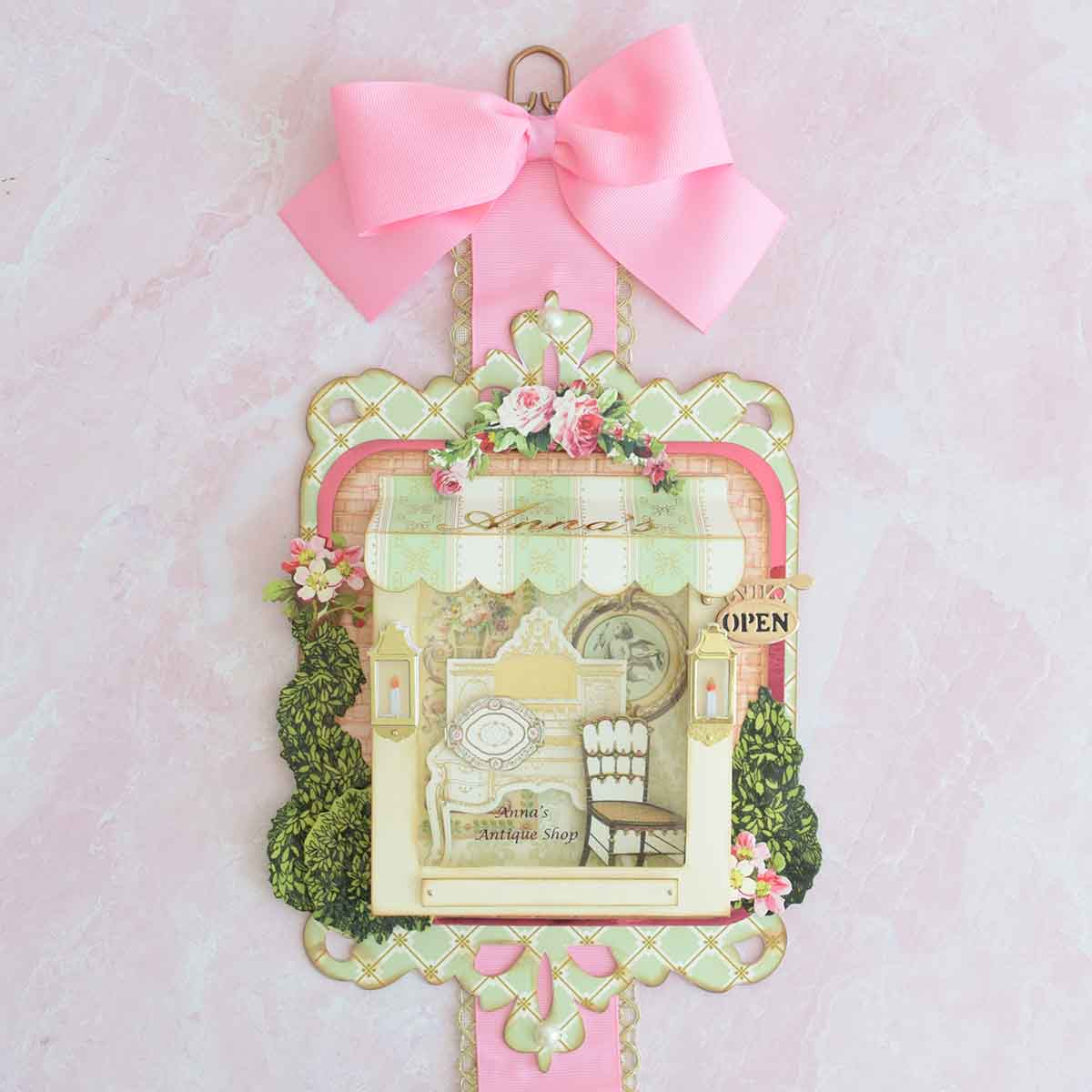 Top tier of Anna's hanging card. Store vignette with antiques, topiaries and flowers.