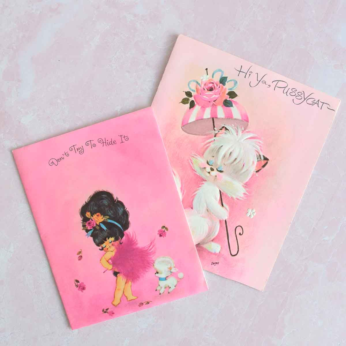 Two pink, vintage cards- one with a little girl and poodle and the other is a cat with an umbrella.